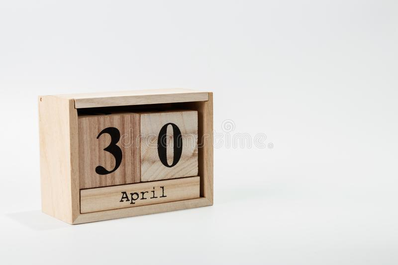 Wooden calendar April 30 on a white background. Close up royalty free stock photo