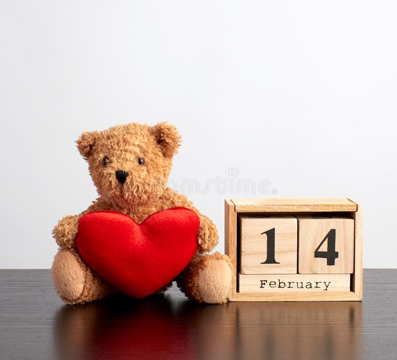 Wooden calendar of cubes with the date of February 14 and a brown teddy bear on a black table. Valentine\'s Day celebration royalty free stock image
