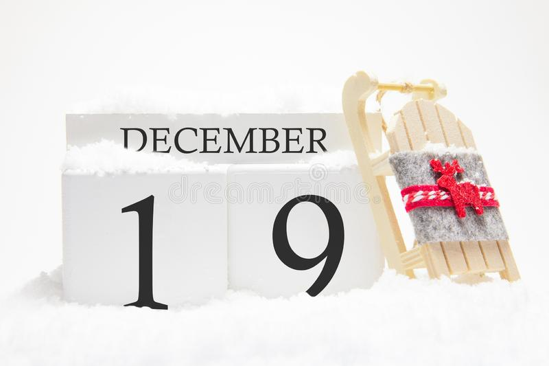Wooden calendar for December, 19 th day of the winter month. The symbols of winter are snow and sleigh. Concept of holidays,. Vacation and winter fun stock photos