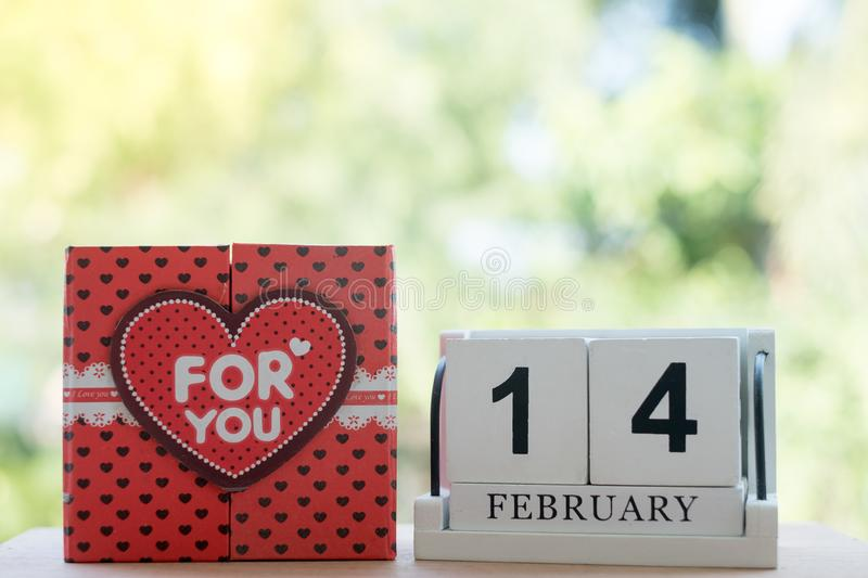 The wooden calendar, 14 February, consists of a box of red hearts that are written for you, placed side by side with a natural stock image