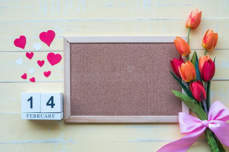 The wooden calendar on 14 February consists of flowers and hearts placed side by side with a yellow background color on Valentine stock images