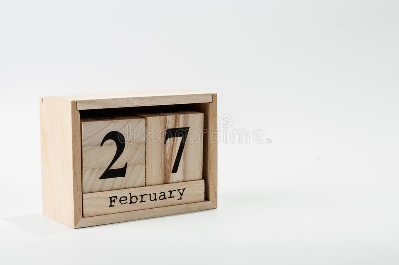 Wooden calendar February 27 on a white background. Close up stock photography