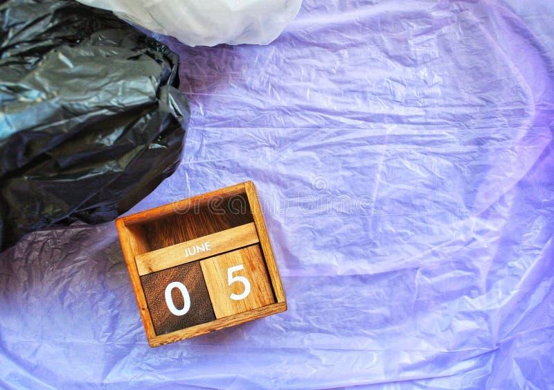 Wooden calendar, 5 June, on a plastic bag background. World environment day. Concept No plastic,Zero - Waste Plastic. Wooden calendar, 5 June, on a plastic bag stock photo
