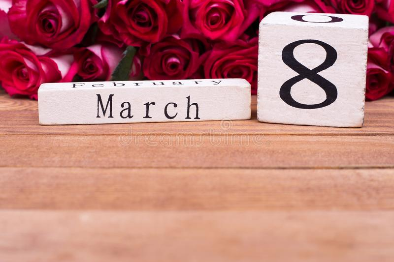 Wooden calendar 8 march, roses, place for text royalty free stock photography