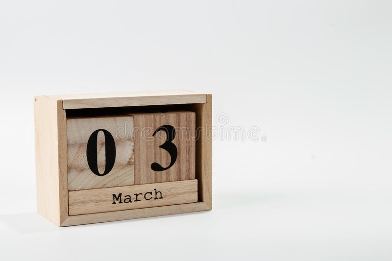 Wooden calendar March 03 on a white background. Close up royalty free stock photo