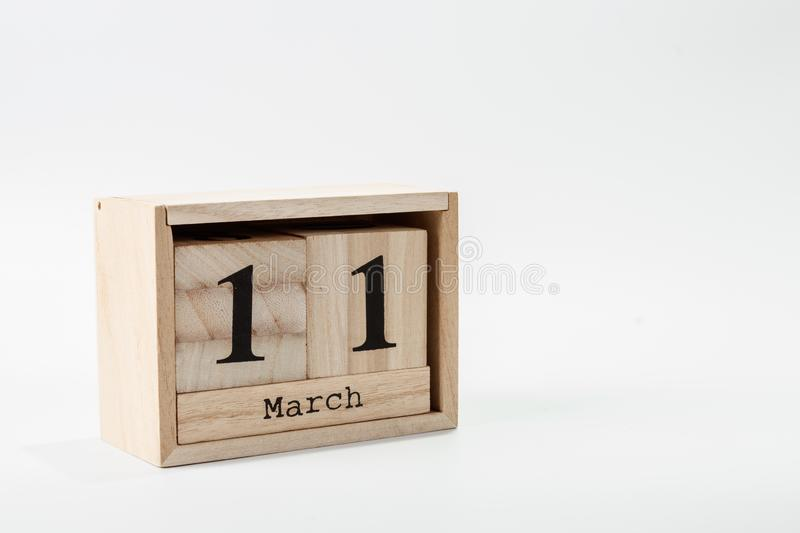Wooden calendar March 11 on a white background. Close up royalty free stock photo
