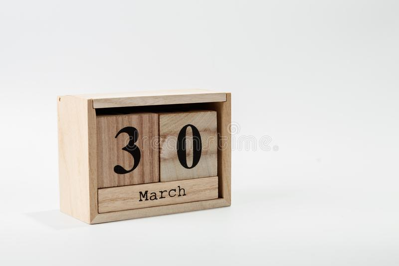 Wooden calendar March 30 on a white background. Close up stock photo