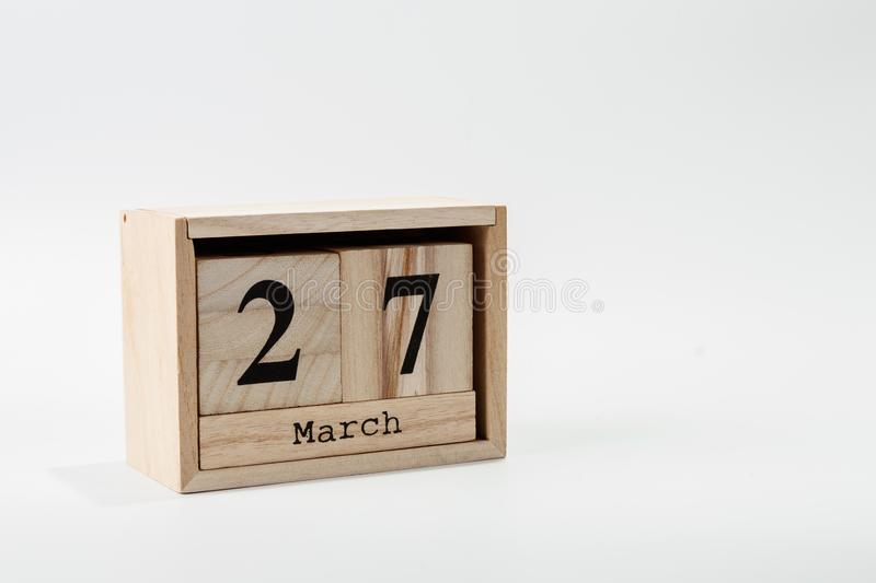 Wooden calendar March 27 on a white background. Close up royalty free stock images