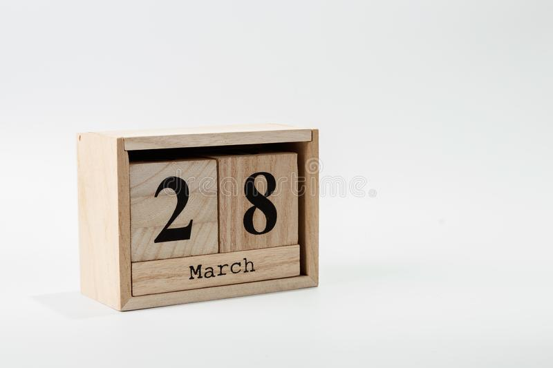 Wooden calendar March 28 on a white background. Close up stock photos