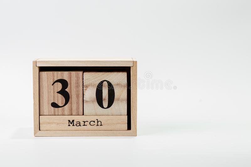 Wooden calendar March 30 on a white background. Close up royalty free stock images