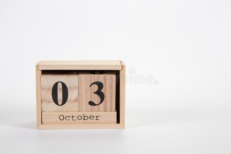 Wooden calendar October 03 on a white background. Close up stock photography