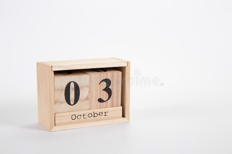 Wooden calendar October 03 on a white background. Close up royalty free stock images