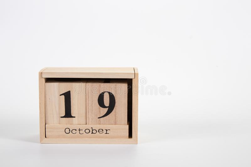 Wooden calendar October 19 on a white background. Close up royalty free stock photography