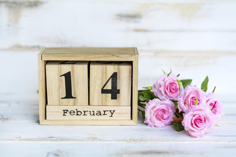 Valentine`s Greeting Card with Roses and Wooden Calendar. Wooden Calendar and Pink Roses for Valentines`s Day royalty free stock photography