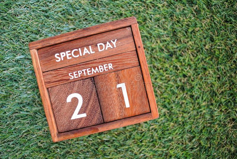 Wooden calendar on September 21 on a green grass background. World peace day. Gray oil gallon on cement background. Iron supplement pills . Zinc is an stock photography