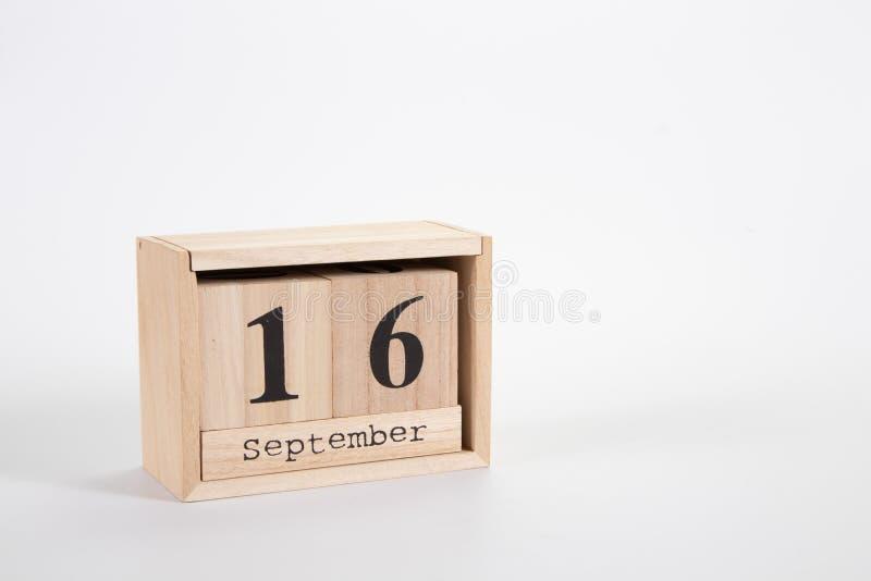 Wooden calendar September 16 on a white background. Close up stock photos