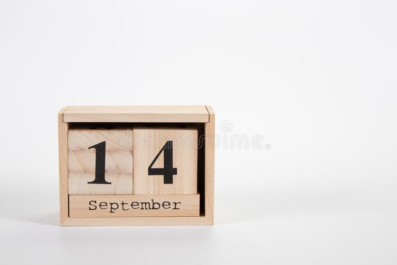 Wooden calendar September 14 on a white background. Close up royalty free stock image