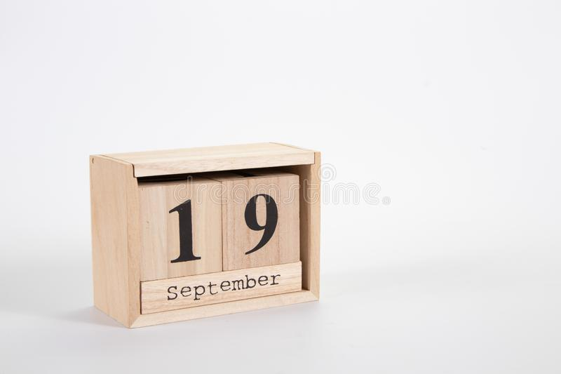 Wooden calendar September 19 on a white background. Close up stock photo