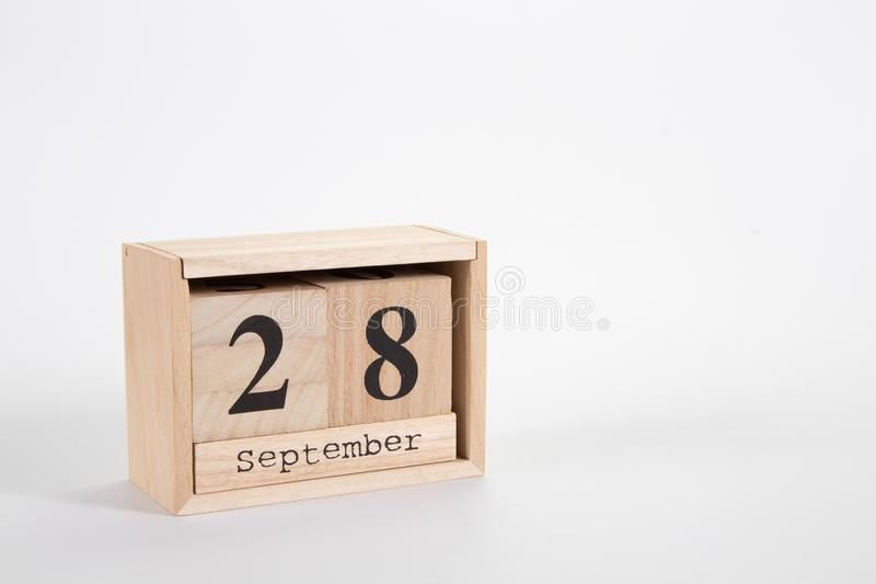 Wooden calendar September 28 on a white background. Close up stock photography