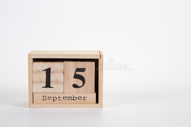 Wooden calendar September 15 on a white background. Close up stock photos