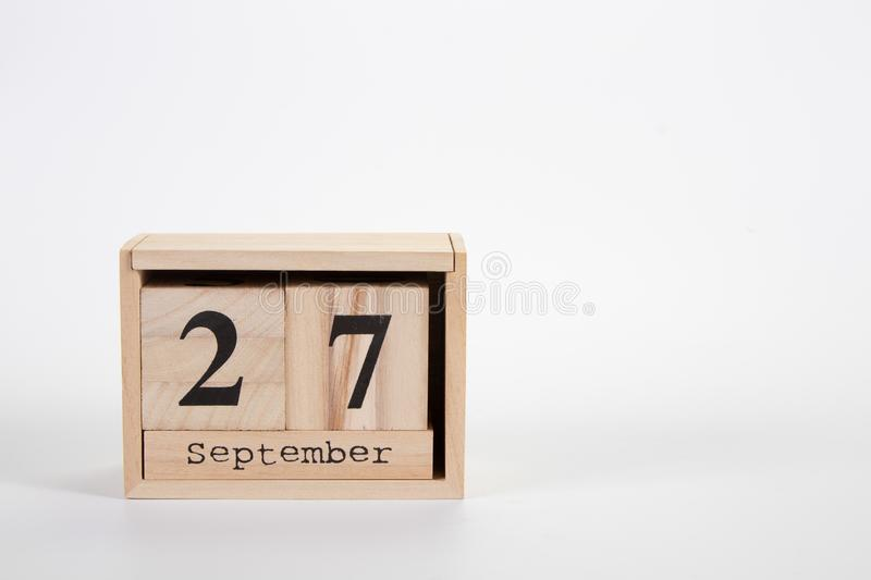 Wooden calendar September 27 on a white background. Close up stock photography