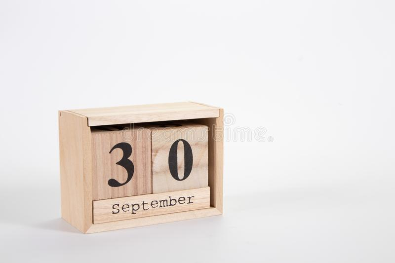 Wooden calendar September 30 on a white background. Close up royalty free stock photo