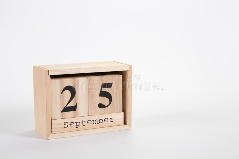 Wooden calendar September 25 on a white background. Close up royalty free stock image