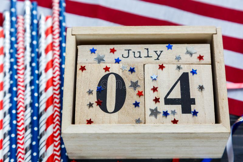 Wooden calendar 4th of July day of American independence, decorations,  flag, candles, straws. USA holiday decorations royalty free stock photos