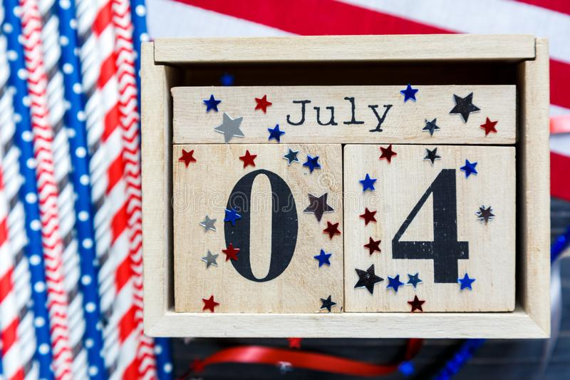 Wooden calendar 4th of July day of American independence, decorations,  flag, candles, straws. USA holiday decorations stock photography