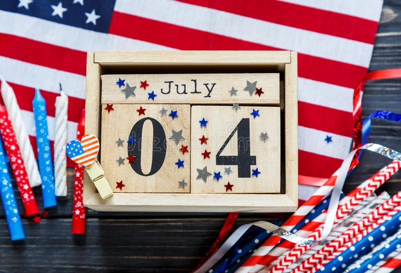 Wooden calendar 4th of July day of American independence, decorations,  flag, candles, straws. USA holiday decorations royalty free stock image