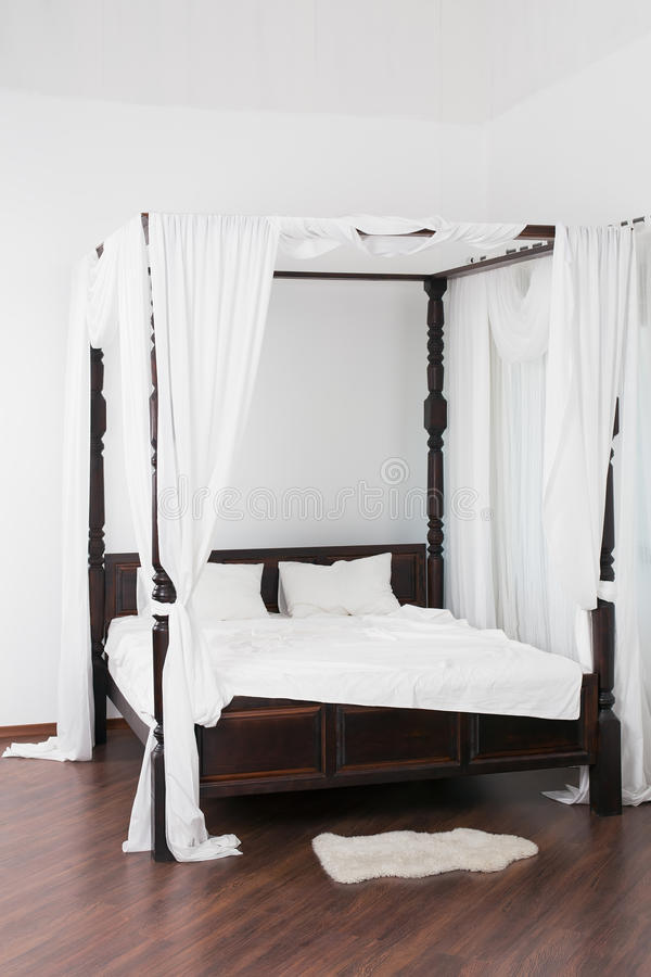 Wooden canopy bed and a white hide on the floor. In a light room stock photography