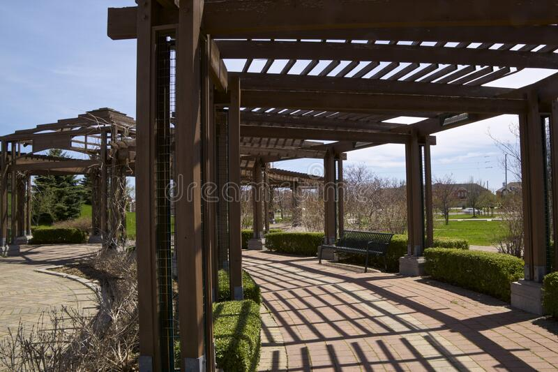 The wooden canopy made of beams - pergola in the patio of public park in Richmond Hill, Ontario, Canada. Richmond Hill, Ontario / Canada - May 08, 2019: The royalty free stock photography