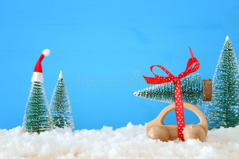 Wooden car carrying a christmas tree with santa hat in front of blue background.. Wooden car carrying a christmas tree with santa hat in front of blue stock photos
