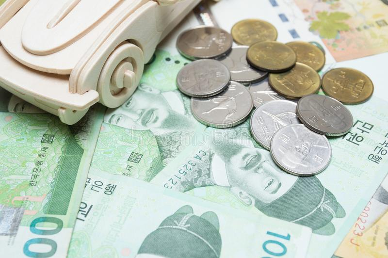 Wooden car and Korean money. Concept for buying, renting, insurance, fuel, service and repair costs. Finance and economy concept stock image