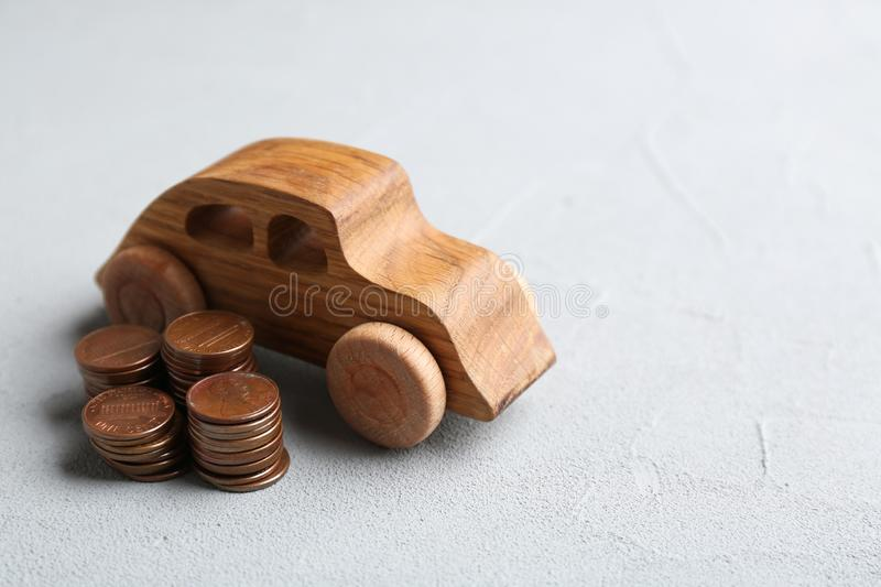 Wooden car model and coins on table. Space for text royalty free stock images