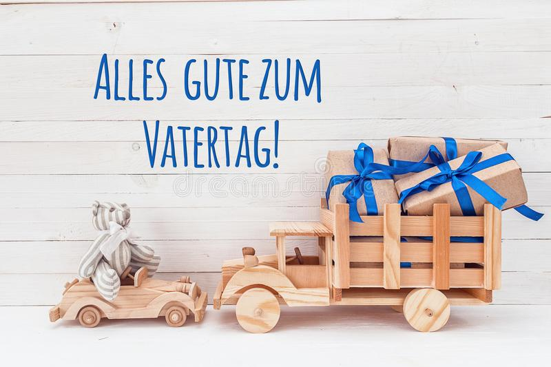 Wooden car with teddy bear and wooden truck with gifts. German g royalty free stock images