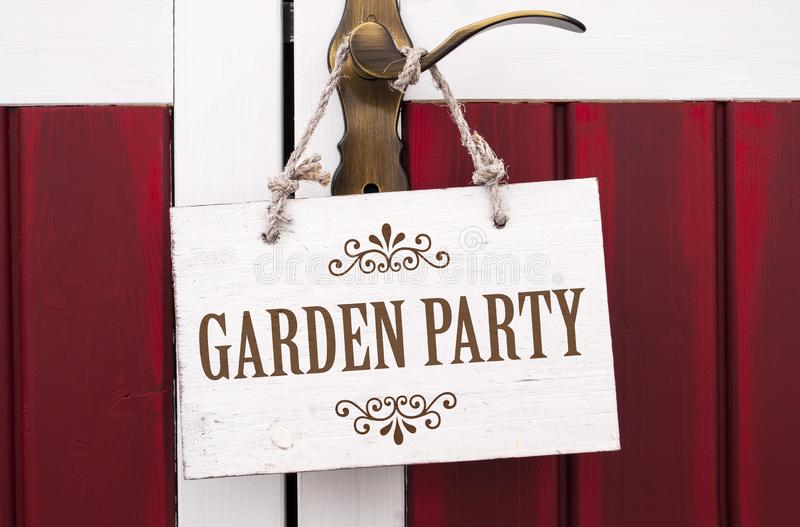 Wooden cardboard and chalkboard with garden party. On a door handle stock photography