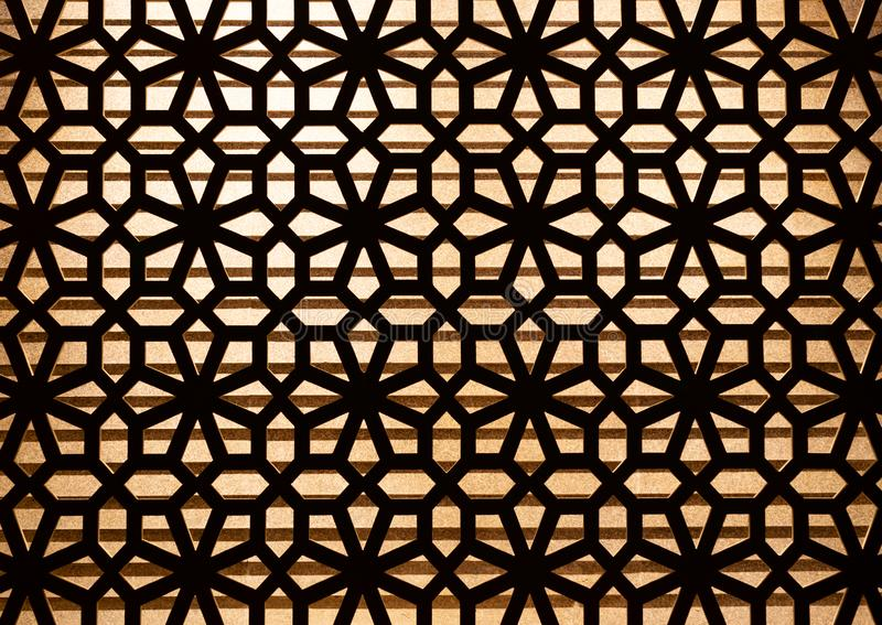 Wooden carve pattern decoration on the wall with lighting in background. stock photography