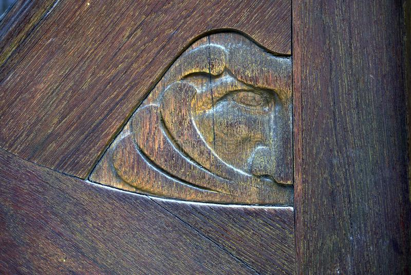 Wooden carved face symbolising the wind. Detail from a wooden door, aged with grace and moss. Symbolising the wind. Developed using darktable 2.6.2 royalty free stock photography