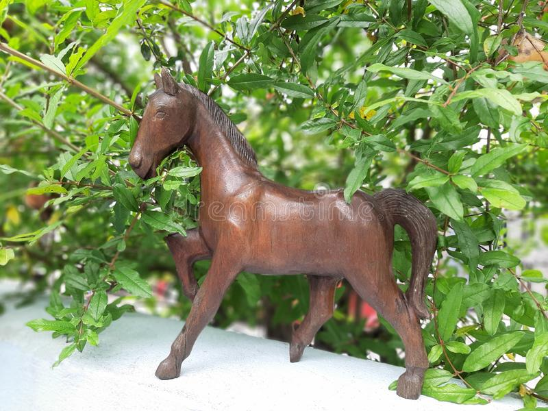 Wooden carved horse and blurred pomegranate tree stock image