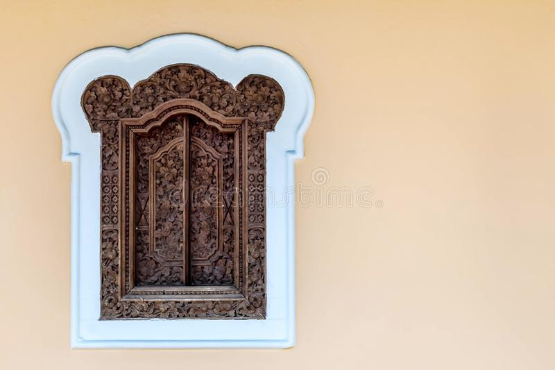 Wooden carved shutters on the window. On a pastel yellow plain wall. Copy space at the right.  stock photography