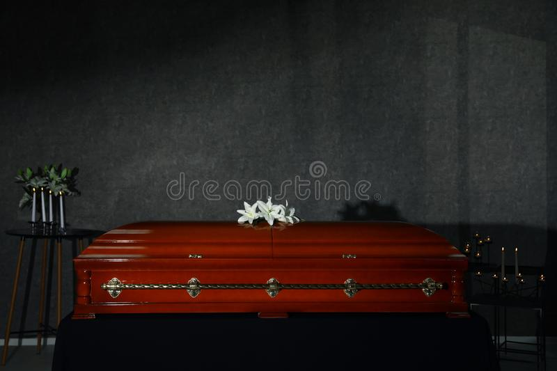 Casket with white lilies and burning candles in funeral home royalty free stock image