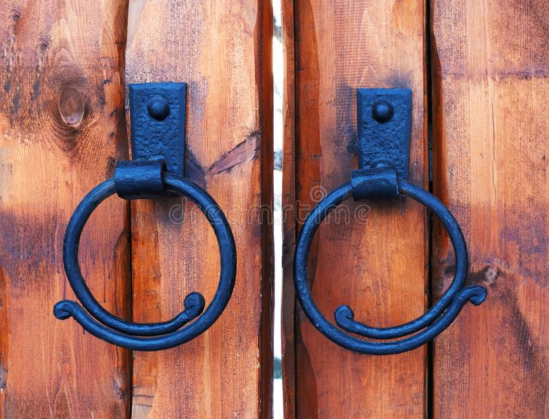 Wooden castle gate. Cast iron antique door handle ring on wood door. royalty free stock photography