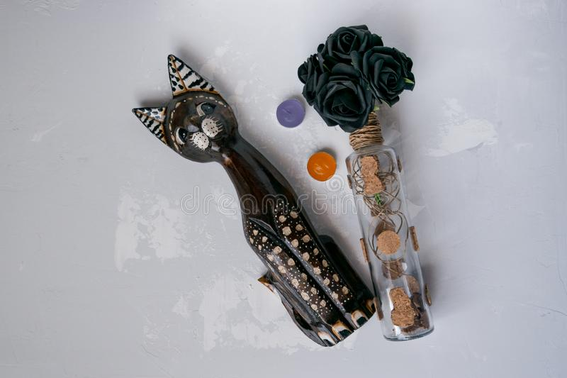 Wooden cat on a gray background with black flowers. In a vase bottle stock images