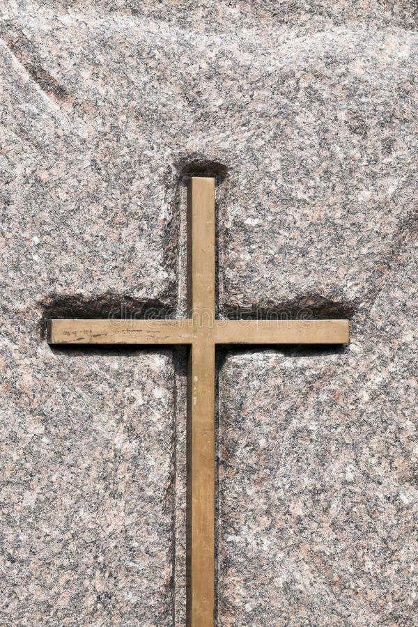 Wooden Catholic cross. A wooden Catholic cross fixed on a stone. Religious symbols close-up photo stock images