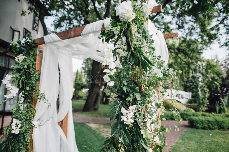 Wooden ceremony arch decoretade by white cloth, flowers and greenery standing in bright garden for wedding ceremony. Decor. stock photos