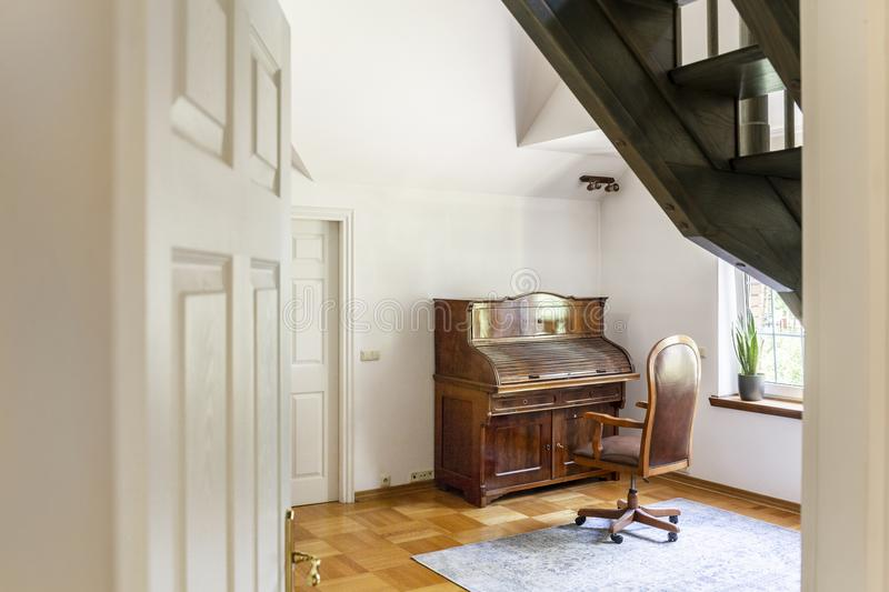 Wooden chair at classic piano in white interior of elegant house. Real photo stock photos