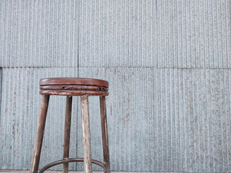 Wooden chair with galvanized walls. royalty free stock images