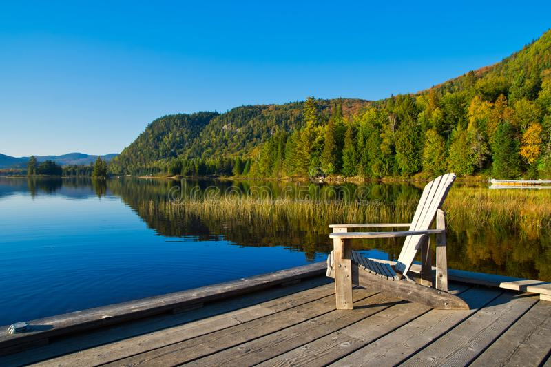 Wooden chair on lakeside pier royalty free stock photo