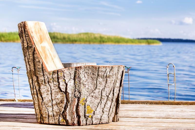 Wooden chair made of big stump on a fishing pier on lake or river royalty free stock photo